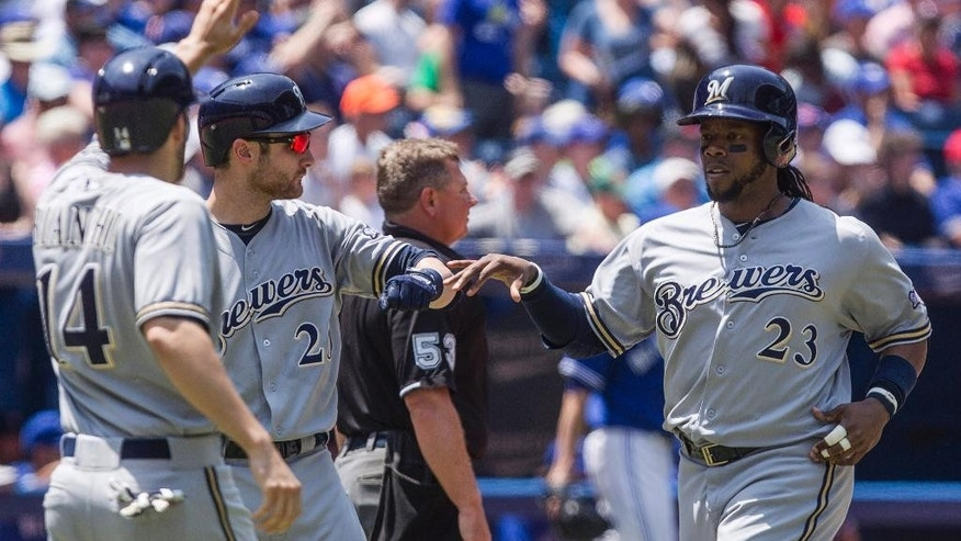 Milwaukee Brewers' Rickie Weeks, right,  and Jeff Bianchi, left, celebrate with Jonathan Lucroy after scoring on a triple by Ryan Braun during third inning interleague baseball action against the Blue Jays in Toronto on Wednesday July 2 , 2014. (AP Photo/The Canadian Press, Chris Young)
