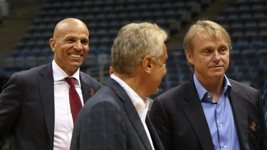 Newly named Milwaukee Bucks head coach Jason Kidd, left, leaves a press conference behind Bucks co-owners Wesley Edens, right, and Marc Lasry, Wednesday, July 2, 2014, in Milwaukee. (AP Photo/Jeffrey Phelps)
