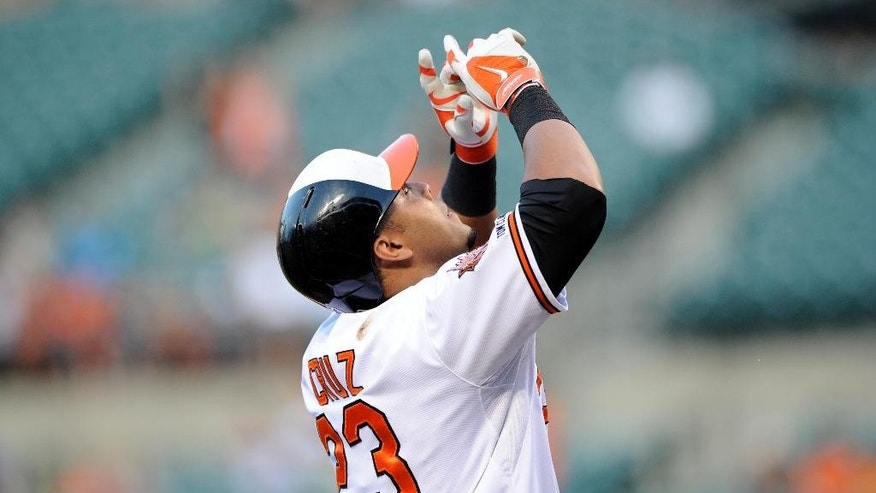 Baltimore Orioles' Nelson Cruz celebrates his home run against the Texas Rangers during the first inning of a baseball game, Tuesday, July 1, 2014, in Baltimore. (AP Photo/Nick Wass)