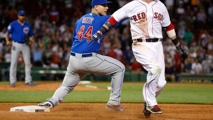 Chicago Cubs first baseman Anthony Rizzo (44) watches while Boston Red Sox's Dustin Pedroia reacts to being called out for the last out of the baseball game in the ninth inning at Fenway Park in Boston, Tuesday, July 1, 2014. The Cubs won 2-1. (AP Photo/Elise Amendola)