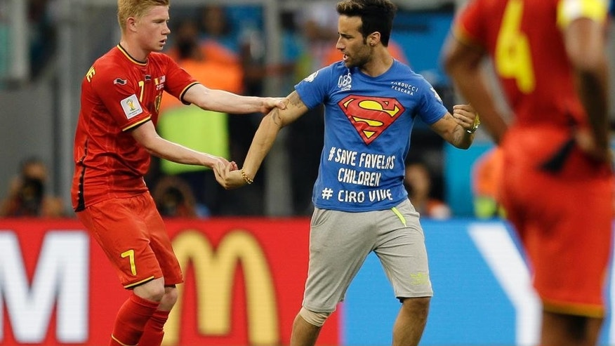 Belgium's Kevin De Bruyne holds on to a spectator who ran on to the pitch during the World Cup round of 16 soccer match between Belgium and the USA at the Arena Fonte Nova in Salvador, Brazil, Tuesday, July 1, 2014. (AP Photo/Natacha Pisarenko)