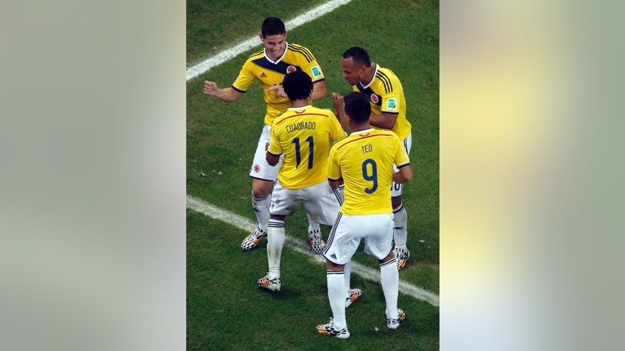 Colombia's James Rodriguez, left, dances as he celebrates with his teammates after scoring his side's second goal during the World Cup round of 16 soccer match between Colombia and Uruguay at the Maracana Stadium in Rio de Janeiro, Brazil, Saturday, June 28, 2014. (AP Photo/Fabrizio Bensch, Pool)