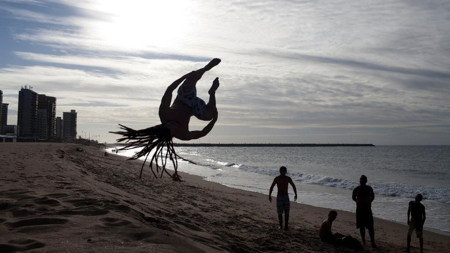 A man does a flip on the beach in Fortaleza, Brazil, Wednesday, July 2, 2014. Fortaleza is one of many cities hosting World Cup soccer matches this month. (AP Photo/Natacha Pisarenko)