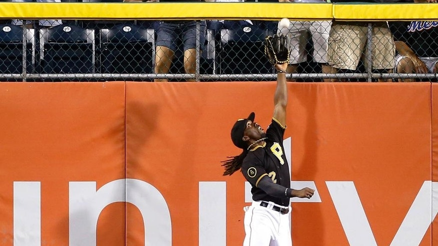 Pittsburgh Pirates center fielder Andrew McCutchen (22) leaps next to the wall to catch a deep fly ball by New York Mets' Curtis Granderson in the eighth inning of a baseball game Friday, June 27, 2014, in Pittsburgh. The Pirates won -3-2 in 11 innings. (AP Photo/Keith Srakocic)