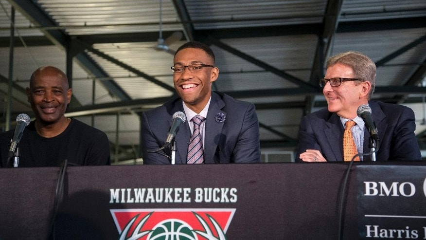 Milwaukee Bucks first round draft pick Jabari Parker is flanked by coach Larry Drew, left, and general manager John Hammond as he is introduced at a news conference Friday, June 27, 2014, in Milwaukee. (AP Photo/Morry Gash)