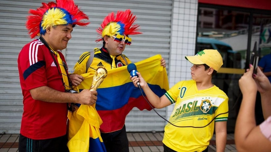 A young man holds a microphone up to fans decked out in the team colors of the Colombian national soccer team as they are interviewed by a television reporter in front of the hotel where the South American team is lodging in Fortaleza, Brazil, Thursday, July 3, 2014. Colombian supporters are in Fortaleza hoping to see some history being made in this northeastern World Cup city where Brazil and Colombia face off in the World Cup quarterfinals, Saturday. (AP Photo/Rodrigo Abd)