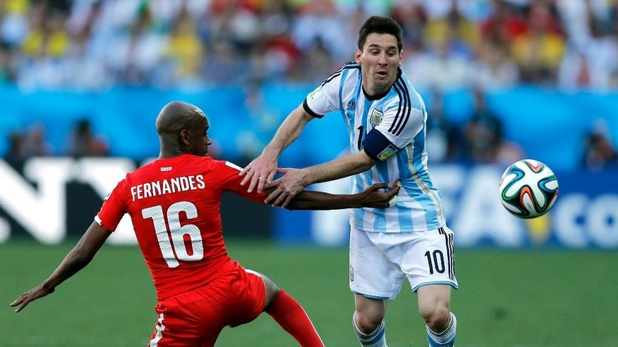 CORRECTS NAME OF MARCOS ROJO TO GELSON FERNANDES - Switzerland's Gelson Fernandes, left, tries to stop Argentina's Lionel Messi during the World Cup round of 16 soccer match between Argentina and Switzerland at the Itaquerao Stadium in Sao Paulo, Brazil, Tuesday, July 1, 2014. (AP Photo/Victor R. Caivano)
