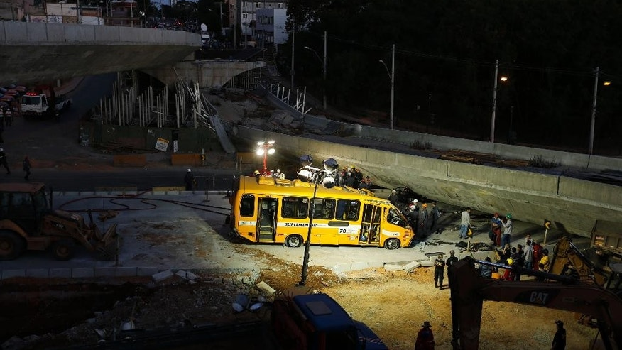 A bus sits damaged next to a bridge after it collapsed in Belo Horizonte, Brazil, Thursday, July 3, 2014. The overpass under construction collapsed Thursday in the Brazilian World Cup host city. The incident took place on a main avenue, the expansion of which was part of the World Cup infrastructure plan but, like most urban mobility projects related to the Cup, was not finished on time for the event. (AP Photo/Victor R. Caivano)