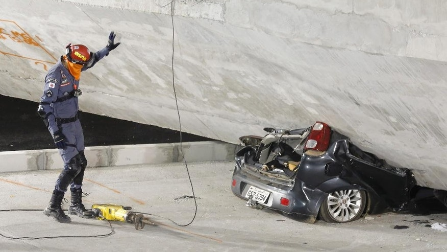 A policeman looks at a car crushed underneath a collapsed bridge in Belo Horizonte, Brazil, Thursday, July 3, 2014. The overpass under construction collapsed Thursday in the Brazilian World Cup host city. The incident took place on a main avenue, the expansion of which was part of the World Cup infrastructure plan but, like most urban mobility projects related to the Cup, was not finished on time for the event. (AP Photo/Victor R. Caivano)