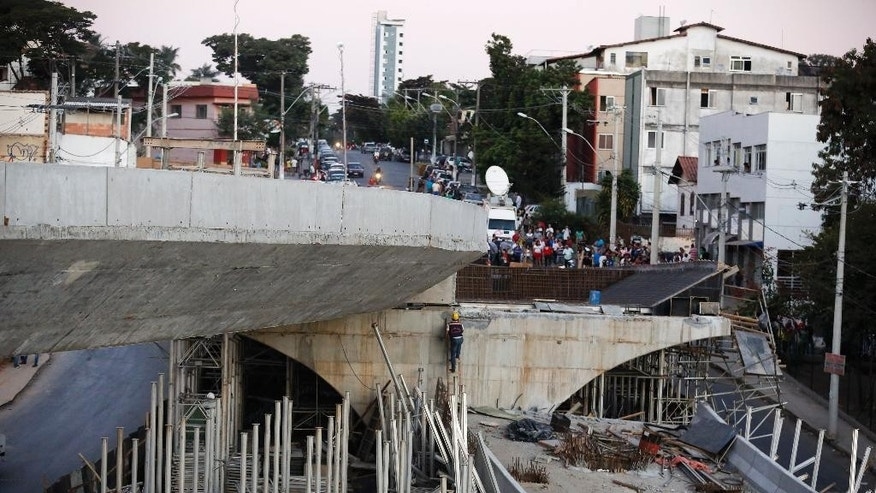 A woker walks up a ladder on a bridge that collapsed in Belo Horizonte, Brazil, Thursday, July 3, 2014. The overpass under construction collapsed Thursday in the Brazilian World Cup host city. The incident took place on a main avenue, the expansion of which was part of the World Cup infrastructure plan but, like most urban mobility projects related to the Cup, was not finished on time for the event. (AP Photo/Victor R. Caivano)