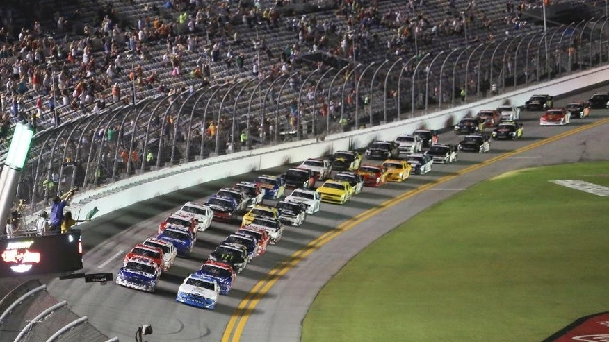 Trevor Bayne, front left, and Dakoda Armstrong, front right, lead the field to start the  NASCAR Nationwide series auto race at Daytona International Speedway in Daytona Beach, Fla., Friday, July 4, 2014. (AP Photo/David Graham)