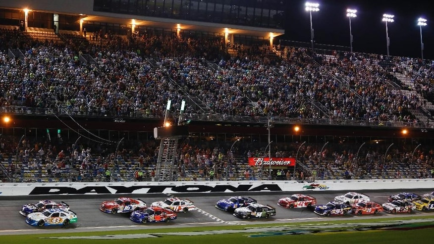 Trevor Bayne, top left, and Dakoda Armstrong (43) lead the field to start the  NASCAR Nationwide series auto race at Daytona International Speedway in Daytona Beach, Fla., Friday, July 4, 2014. (AP Photo/Terry Renna)