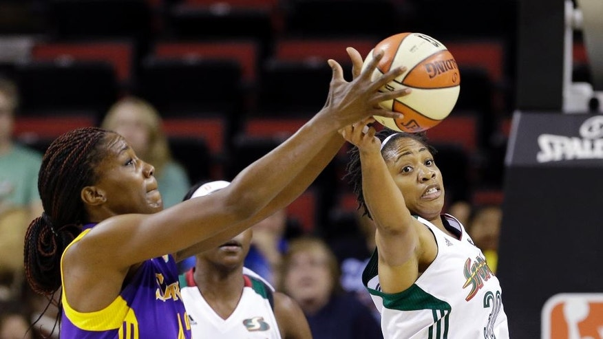 Los Angeles Sparks' Jantel Lavender, left, and Seattle Storm's Tanisha Wright reach for the ball in the first half of a WNBA basketball game Thursday, July 3, 2014, in Seattle. (AP Photo/Elaine Thompson)