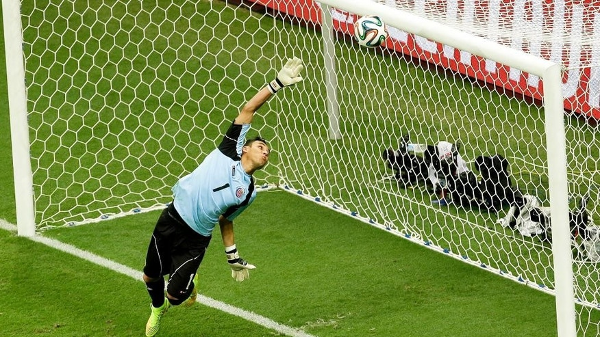 Costa Rica's goalkeeper Keylor Navas dives as the ball hits the bar during the World Cup quarterfinal soccer match between the Netherlands and Costa Rica at the Arena Fonte Nova in Salvador, Brazil, Saturday, July 5, 2014. (AP Photo/Themba Hadebe)