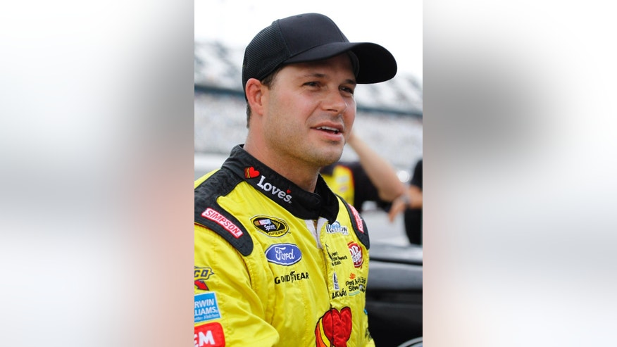David Gilliland talks with reporters after qualifying for the pole position in the NASCAR Sprint Cup Series auto race after the event was shortened due to rain at Daytona International Speedway in Daytona Beach, Fla., Friday, July 4, 2014. (AP Photo/Terry Renna)