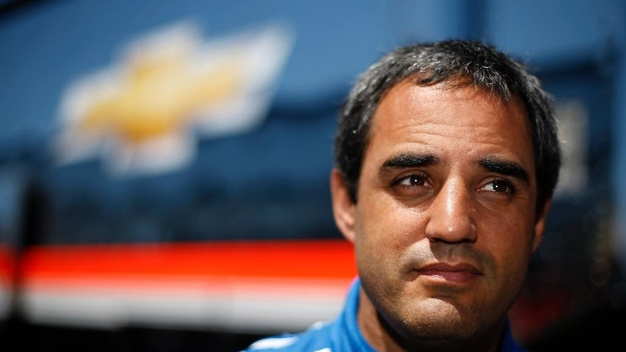 IndyCar driver Juan Pablo Montoya, of Colombia, listens to a reporter's question during an interview after a practice session for Sunday's Pocono IndyCar 500 auto race, Saturday, July 5, 2014, in Long Pond, Pa. (AP Photo/Matt Slocum)