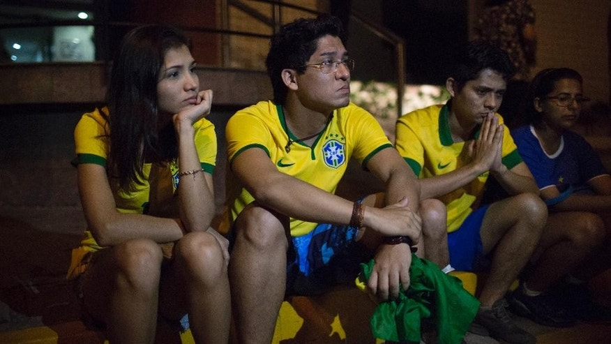 Brazil soccer fans sit outside the Sao Carlos hospital where Brazil's soccer player Neymar was taken after being injured during the World Cup quarterfinal soccer match between Brazil and Colombia, in Fortaleza, Brazil, Friday, July 4, 2014. Brazil's team doctor says Neymar will miss the rest of the World Cup after breaking a vertebrae during the team's 2-1 win. (AP Photo/Renata Brito)