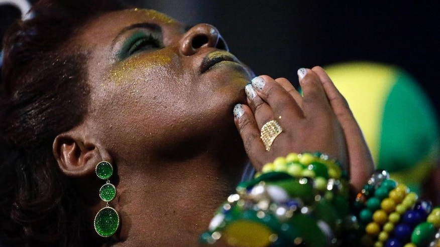 A Brazil soccer fan prays as she watches a live telecast of the World Cup quarterfinal match between Brazil and Colombia inside the FIFA Fan Fest area in Sao Paulo, Brazil, Friday, July 4, 2014. Not long after celebrating another all-important win at the World Cup, Brazil was jolted by the loss of Neymar who fractured a vertebra in his back during the game. The injury has ruled the striker out of the rest of the competition, dealing a massive blow to the team's chances of finally winning a World Cup at home.  (AP Photo/Nelson Antoine)