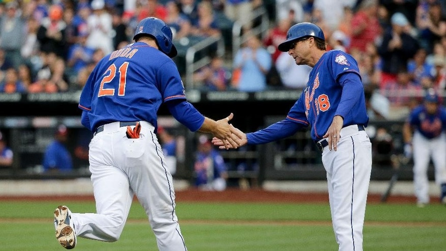 New York Mets' Lucas Duda (21) is greeted by third base coach Tim Teufel (18) while rounding the bases after hitting a two-run home run against the Texas Rangers in the first inning of a baseball game on Friday, July 4, 2014, in New York. Duda's hit was initially called a double but then ruled a home run after review by umpires. (AP Photo/Julie Jacobson)