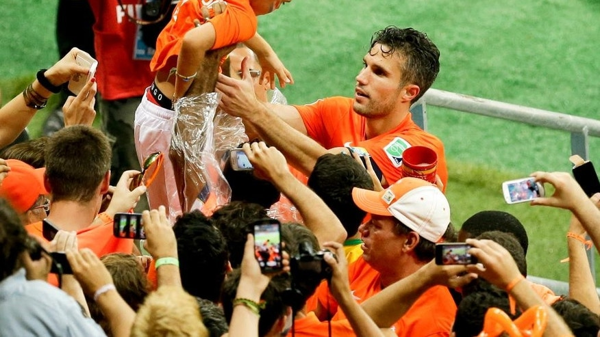 Netherlands' Robin van Persie holds a boy as he celebrates with fans after winning the World Cup quarterfinal soccer match between the Netherlands and Costa Rica at the Arena Fonte Nova in Salvador, Brazil, Saturday, July 5, 2014. Netherlands beat Costa Rica 4-3 on penalties to reach semifinals of the World Cup. (AP Photo/Themba Hadebe)
