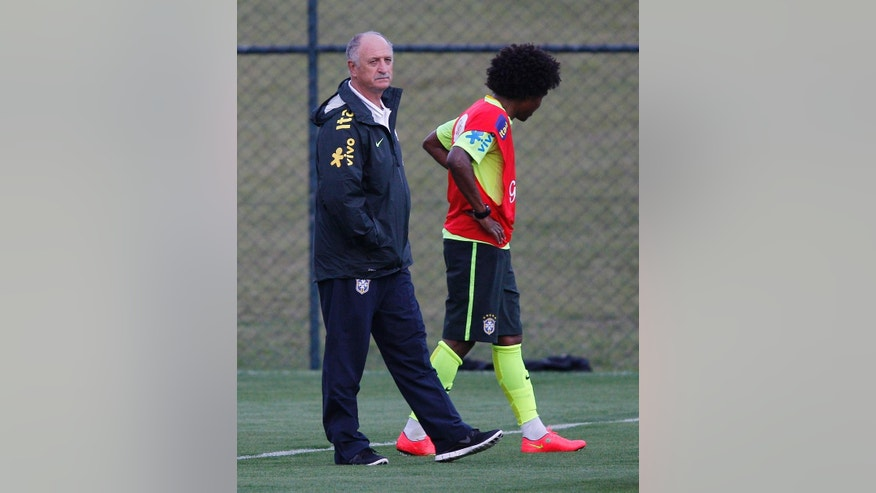 Brazil's Willian leaves the practice session as head coach Luiz Felipe Scolari walks by his side, at the Granja Comary training center in Teresopolis, Brazil, Saturday, July 5, 2014. Brazil will play in the semifinals of the 2014 Soccer World Cup on Tuesday, July 8. (AP Photo/Leo Correa).