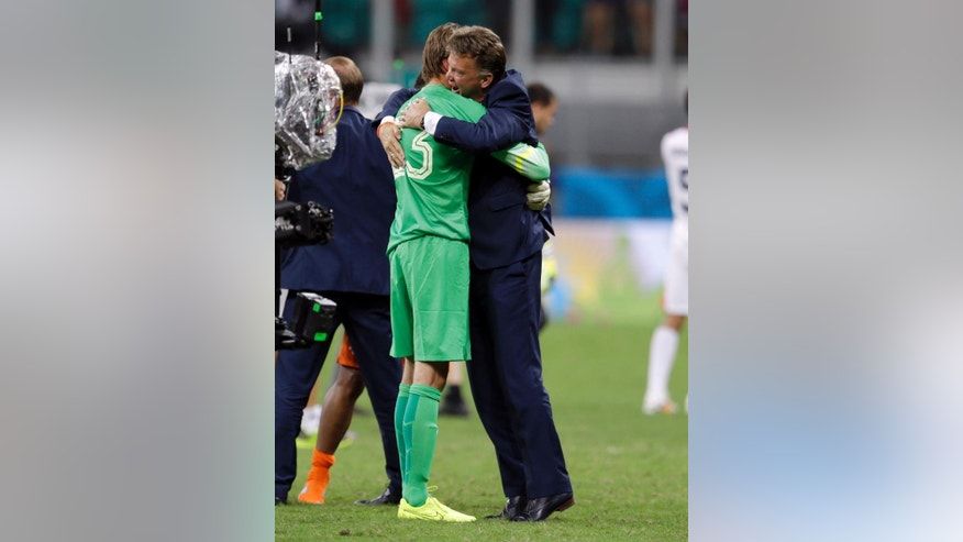 Netherlands' head coach Louis van Gaal hugs goalkeeper Tim Krul after the Netherlands defeated Costa Rica 4-3 in a penalty shootout after a 0-0 tie during the World Cup quarterfinal soccer match at the Arena Fonte Nova in Salvador, Brazil, Saturday, July 5, 2014. (AP Photo/Natacha Pisarenko)