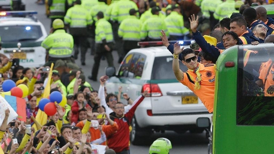 Colombia's soccer player James Rodriguez waves to supporters as he and his teammates are welcomed home from the World Cup, in Bogota, Colombia, Sunday, July 6, 2014. Thousands of fans turned out for the Sunday homecoming of Rodriguez, his teammates and coach Jose Pekerman following their 2-1 loss to Brazil in the quarterfinals on Friday. (AP Photo/Fernando Vergara)