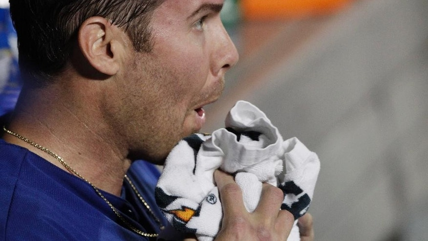 Texas Rangers pitcher Colby Lewis towels off his face after completing the sixth inning against the New York Mets in a baseball game at Citi Field, Saturday, July 5, 2014, in New York. (AP Photo/Mark Lennihan)
