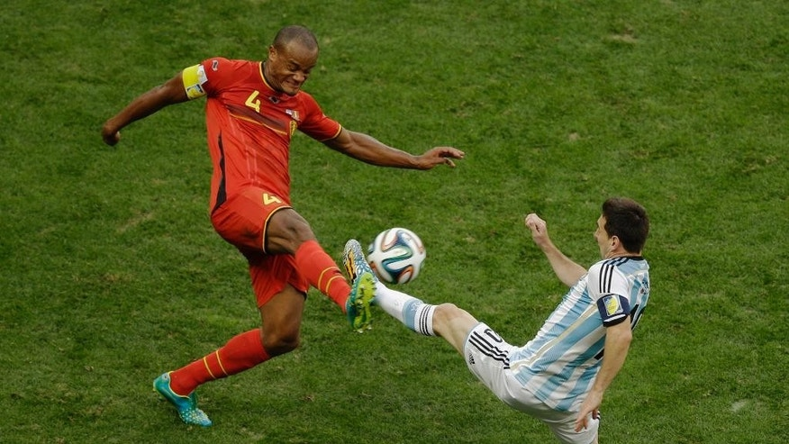 Belgium's Vincent Kompany, left,  and Argentina's Lionel Messi fight for the ball during the World Cup quarterfinal soccer match between Argentina and Belgium at the Estadio Nacional in Brasilia, Brazil, Saturday, July 5, 2014. (AP Photo/Thanassis Stavrakis)