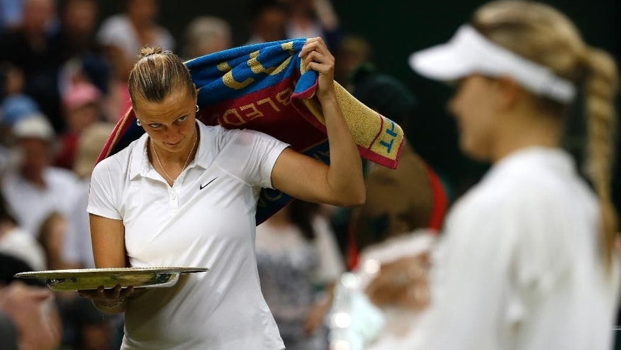 Petra Kvitova of the Czech Republic, left, looks across at Eugenie Bouchard of Canada during the trophy ceremony after winning the women's singles final match at the All England Lawn Tennis Championships in Wimbledon, London, Saturday, July 5, 2014. (AP Photo/Sang Tan)