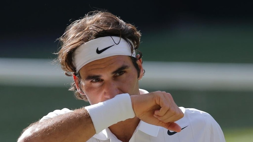 Roger Federer of Switzerland wipes his face with his wrist band as he plays against Novak Djokovic of Serbia during their men's singles final match at the All England Lawn Tennis Championships in Wimbledon, London, Sunday, July 6, 2014. (AP Photo/Pavel Golovkin)