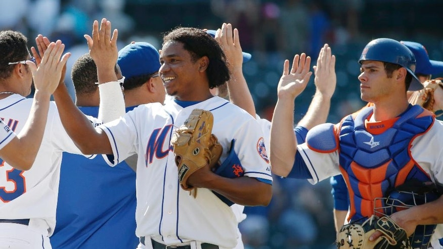 Teammates congratulate New York Mets relief pitcher Jenrry Mejia, center, and Mets backup catcher Anthony Recker, right, after Mejia  closed out the Mets 8-4 victory over the Texas Rangers in an interleague baseball game in New York, Sunday, July 6, 2014. (AP Photo/Kathy Willens)