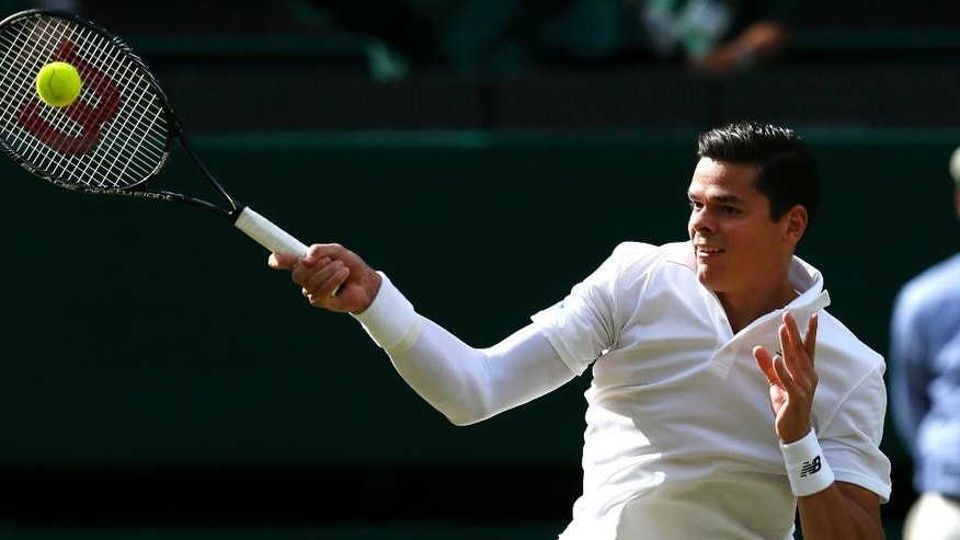 Milos Raonic of Canada plays a return to  Roger Federer of Switzerland during their men's singles semifinal match at the All England Lawn Tennis Championships in Wimbledon, London, Friday, July 4, 2014. (AP Photo/Ben Curtis)