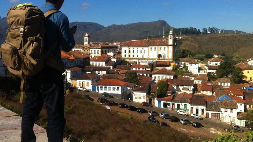 In this June 25, 2014, photo, a backpacker gets an overview of the town of Ouro Preto, Brazil. Following a road that climbs southeast through mist-shrouded hills and valleys, visitors approaching Ouro Preto first see the red-tiled roofs of its whitewashed colonial buildings before reaching the town's cobblestoned streets and its astonishing 18th century Baroque church, a tribute to the riches of gold and gems extracted for the country's former colonial masters. (AP Photo/Frank Griffiths)
