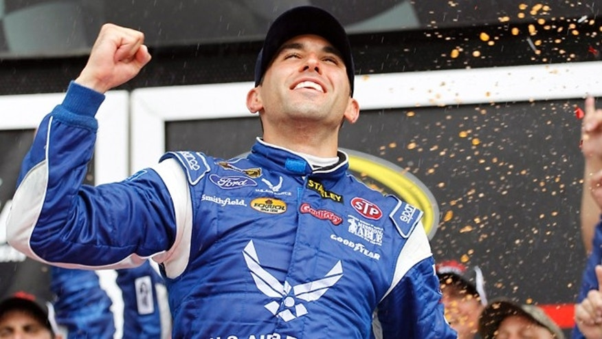 Aric Almirola celebrates in Victory Lane after winning the NASCAR Sprint Cup Series auto race at Daytona International Speedway in Daytona Beach, Fla., Sunday, July 6, 2014.