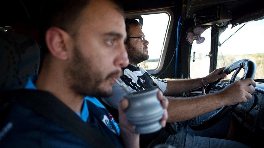"In this Sunday, July 6, 2014 photo, devoted soccer fans of Argentina's national soccer team, Facundo Morales, 30, sips from a mate tea cup as Jose Ribeti, 29, drives their bus penned ""Carnavalito"" from Brasilia to Sao Paulo, Brazil, to watch the semifinal match against Germany. The bus, formerly used for public transport, is outfitted for a long road tour with four single beds, an eating area, and cabinets for storing gear. (AP Photo/Rodrigo Abd)"
