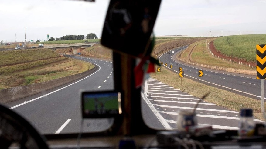 "In this Monday, July 7, 2014 photo, Brazilian highways and sugar cane fields are framed in the windshield of the bus penned ""Carnavalito,"" on the road between Brasilia and Sao Paulo, Brazil. A group of  Argentine men pooled funds to buy the bus for $15,000, and saved up vacation time up over two years to travel all over Brazil in the converted bus to watch their national soccer squad's progress during the World Cup. (AP Photo/Rodrigo Abd)"