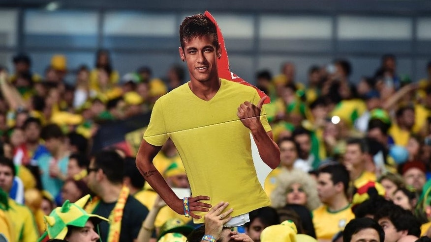 A Brazil supporter holds up a cutout of Brazil's injured star Neymar before the World Cup semifinal soccer match between Brazil and Germany at the Mineirao Stadium in Belo Horizonte, Brazil, Tuesday, July 8, 2014. (AP Photo/Martin Meissner)