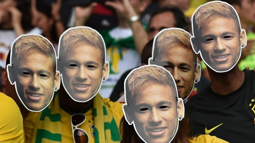 Brazil supporters wear masks of injured Brazilian player Neymar before the World Cup semifinal soccer match between Brazil and Germany at the Mineirao Stadium in Belo Horizonte, Brazil, Tuesday, July 8, 2014. (AP Photo/Martin Meissner)