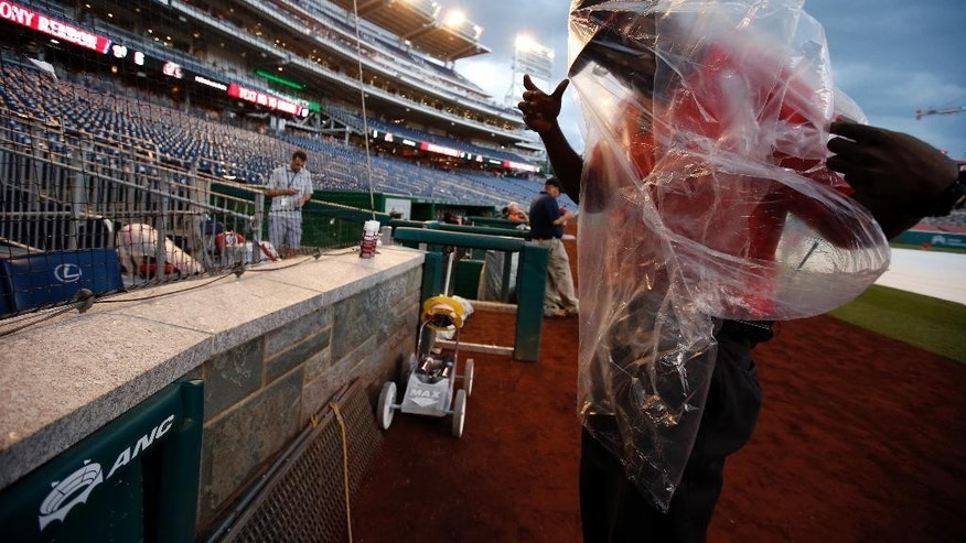 Field security officer Sam Richards works to put on his poncho as the wind picks up during a rain delayed start of an interleague baseball game between the Washington Nationals and the Baltimore Orioles at Nationals Park, Tuesday, July 8, 2014, in Washington. (AP Photo/Alex Brandon)