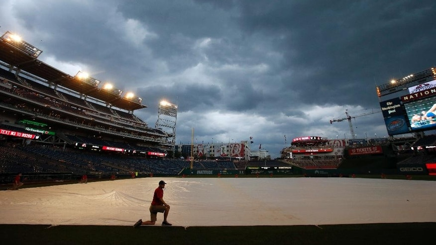 A member of the grounds crew kneels on the tarp during a rain delayed start of an interleague baseball game between the Washington Nationals and the Baltimore Orioles at Nationals Park, Tuesday, July 8, 2014, in Washington. (AP Photo/Alex Brandon)