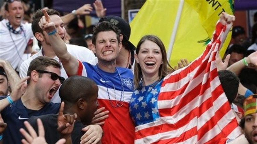 Fans celebrate as the United States scores a goal against Portugal while watching a World Cup soccer match, Sunday, June 22, 2014, in Orlando, Fla. (AP Photo/John Raoux)