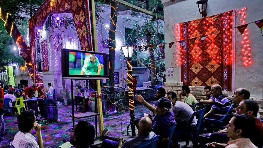 In this Monday, June 30, 2014 photo, soccer fans watch the World Cup match between Germany and Algeria at a cafe in Cairo, Egypt. Politics and conflict are never far from soccer in the Middle East, but this year's World Cup has been entangled with unprecedented sectarian violence and soaring tensions between Arab countries, pushing fans to watch matches in secret or even on a channel owned by region's number one enemy _ Israel. (AP Photo/Ahmed Abd El Latif, El Shorouk Newspaper) EGYPT OUT