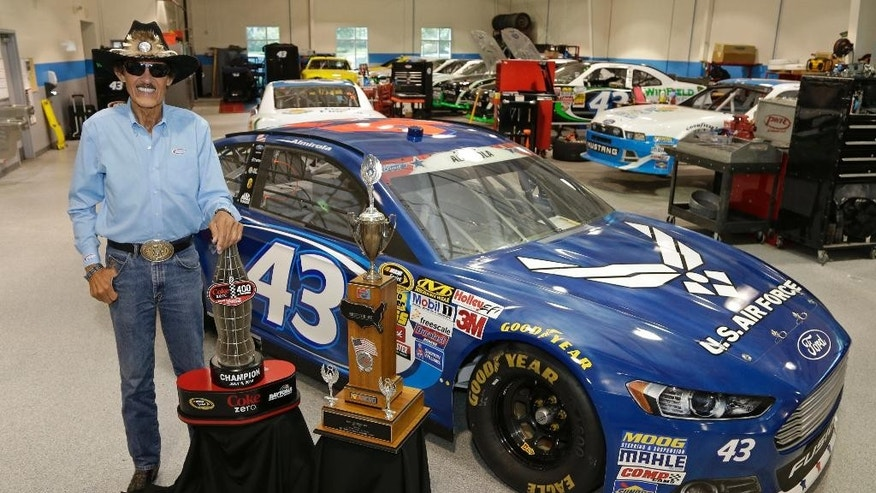 In this July 8, 2014 photo Richard Petty poses with two trophies at the race team's shop in Concord, N.C., Aric Almirola's trophy, left, for winning the Coke Zero 400 NASCAR auto race and his trophy, right, for winning the Firecracker 400 auto race 30 years ago. Almirola put the No. 43 car made famous by owner Richard Petty in Victory Lane for the first time in 544 races. (AP Photo/Chuck Burton)