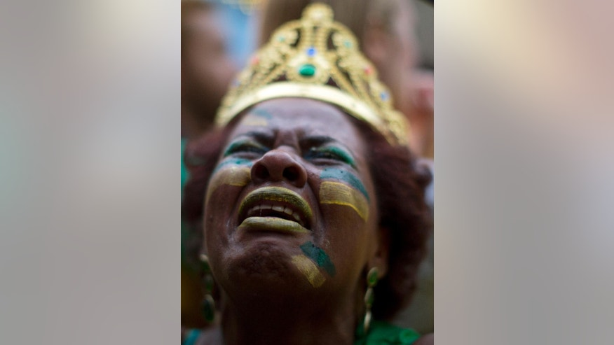 A Brazil soccer fan weeps as she watches Germany score repeatedly against Brazil at a World Cup semifinal match on a live telecast inside the FIFA Fan Fest area in Sao Paulo, Brazil, Tuesday, July 8, 2014. (AP Photo/Dario Lopez-Mills)