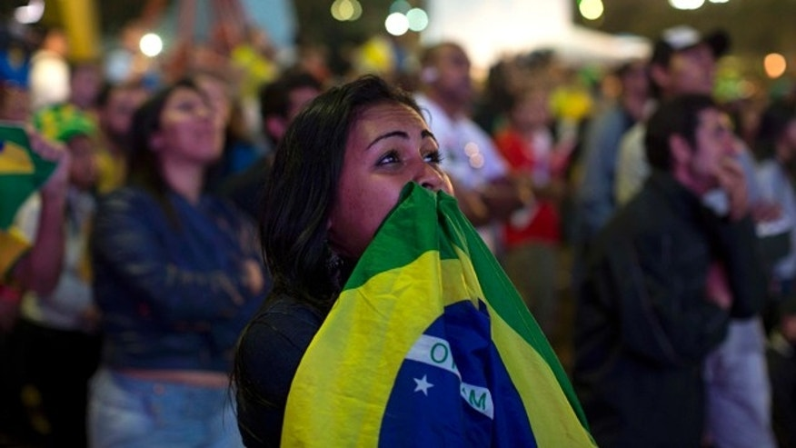 July 8, 2014: A fan of Brazil watches her team lose to Germany in a semi-final match of the 2014 soccer World Cup at the FIFA Fan Fest in Sao Paulo. (AP Photo/Dario Lopez-Mills)