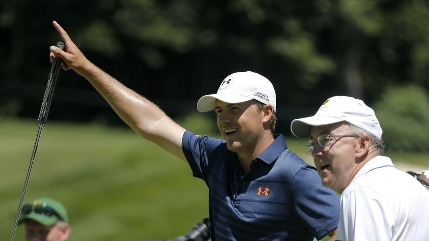 Jordan Spieth, left, signals a great putt by one of his amateur teammates including Sam Allen, Chairman and Chief Executive Officer, Deere & Company, right, during the Pro-Am round of the 2014 John Deere Classic golf tournament at TPC Deere Run in Silvis, Ill., Wednesday, July 9, 2014. (AP Photo/Charles Rex Arbogast)