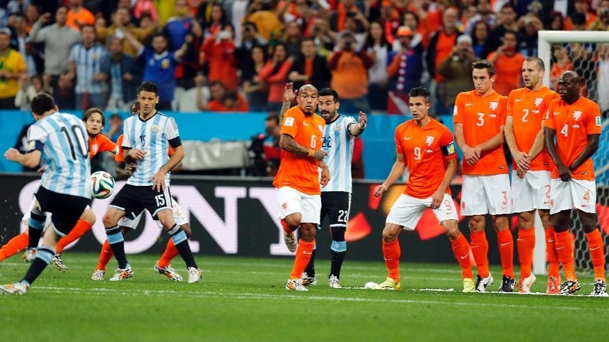 Argentina's Lionel Messi, left, shoots a free-kick past the Dutch defense during the World Cup semifinal soccer match between the Netherlands and Argentina at the Itaquerao Stadium in Sao Paulo, Brazil, Wednesday, July 9, 2014. (AP Photo/Frank Augstein)