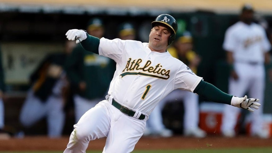Oakland Athletics' Nick Punto slides to score against the San Francisco Giants in the third inning of a baseball game Tuesday, July 8, 2014, in Oakland, Calif. Punto scored on a double by A's Coco Crisp. (AP Photo/Ben Margot)