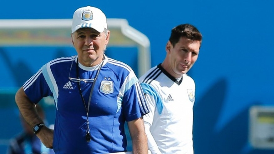Argentina's Lionel Messi, right, walks by Argentina's head coach Alejandro Sabella during a training session at Itaquerao Stadium in Sao Paulo, Brazil, Monday, June 30, 2014. On Tuesday, Argentina will face Switzerland in their next World Cup soccer match.  (AP Photo/Victor R. Caivano)